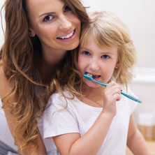 Mom with child brushing teeth